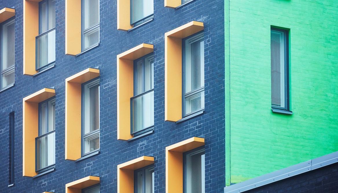 Asianajotoimisto Kak-laki Kiinteistöjuridiikan asiantuntijoita, tässä kuvituskuvassa raikkaan värinen rakennus
