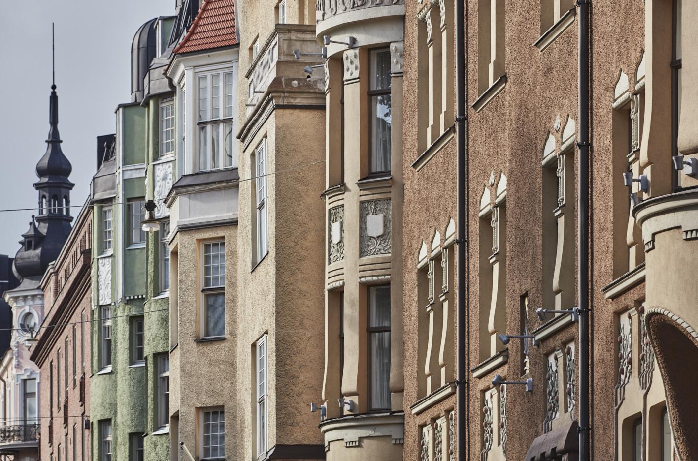 Asianajotoimisto Kuhanen Asikainen Kanerva etusivun kuvituskuvassa ruskean ja keltaisen sävyisiä taloja Helsingissä